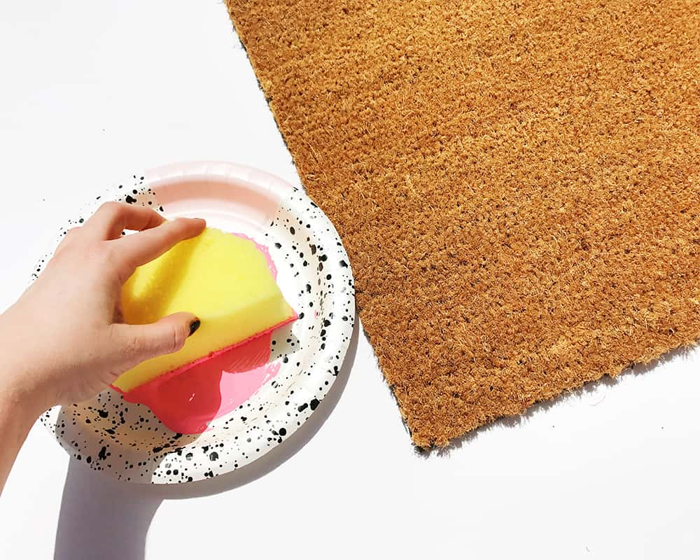 Apply paint to doormat with sponge